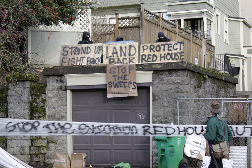 Masked protesters by an occupied home speak with a neighborhood resident opposed to their encampment and demonstration in Portland, Ore., on Wednesday...
