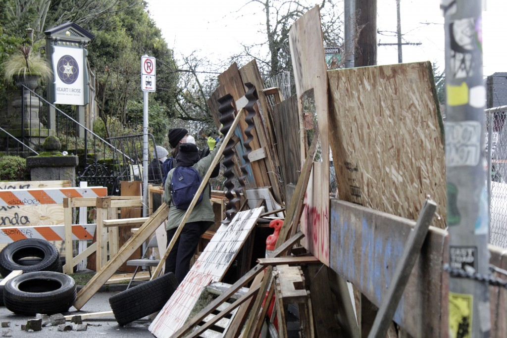 Protesters reinforce their barricades at an encampment outside a home in Portland, Ore., on Wednesday, Dec. 9, 2020. Makeshift barricades erected by p...