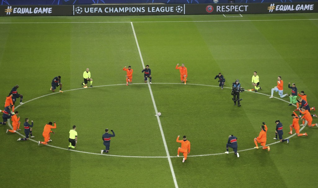 Basaksehir and PSG players take a knee before the start of the Champions League group H soccer match between Paris Saint Germain and Istanbul Basakseh...