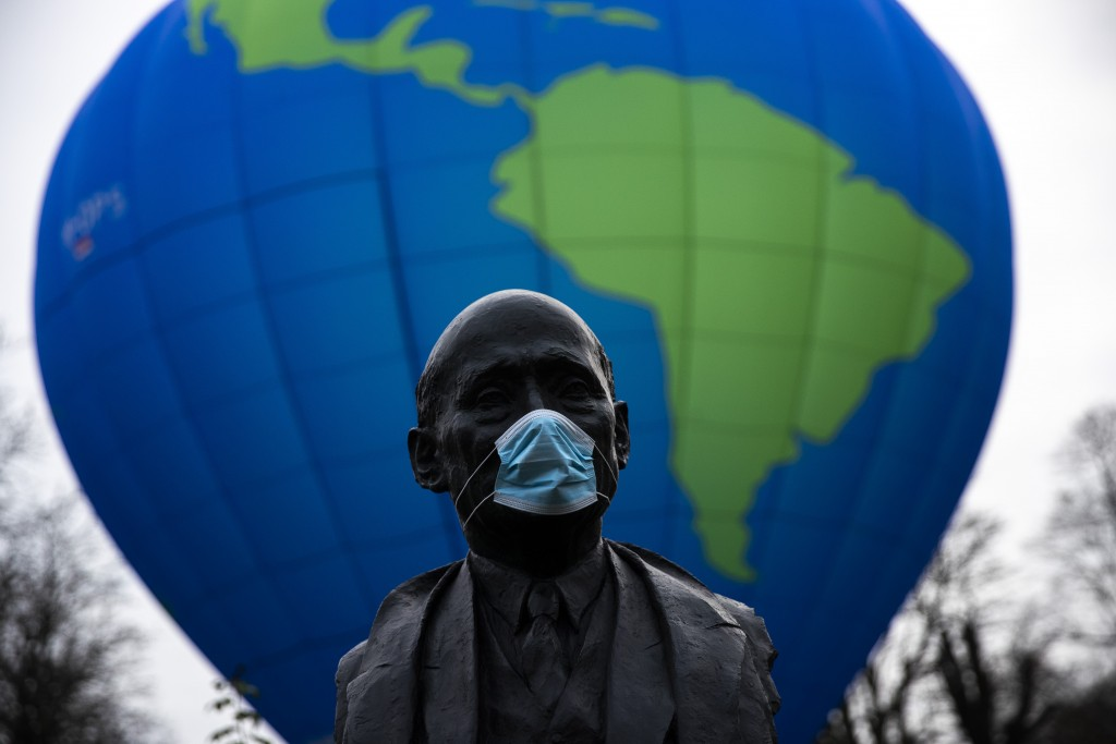 The bust of French statesman Robert Schuman, one of the founders of the European Union, is seen while environmental activists launch a hot air balloon...