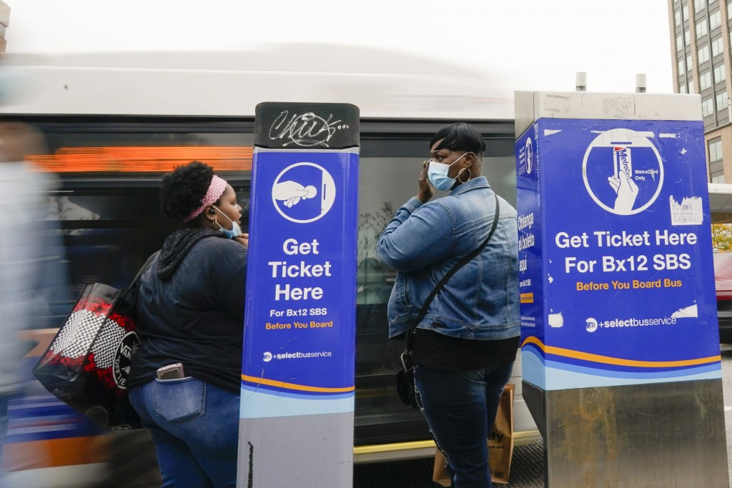 People wear protective masks during the coronavirus pandemic as a bus arrives near the Fordham Metro North station Thursday, Oct. 22, 2020, in New Yor...