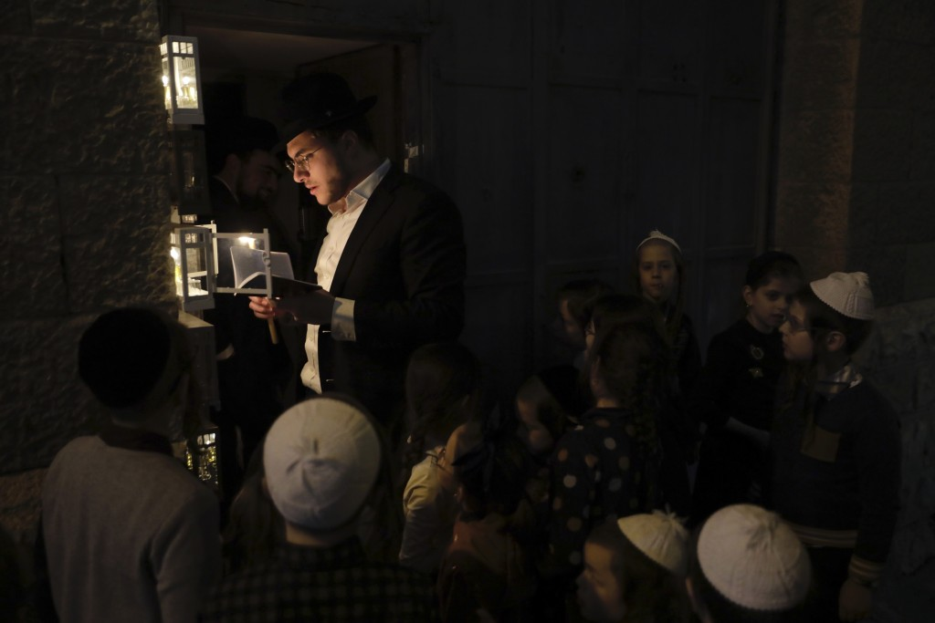 An ultra-Orthodox Jewish man lights candles on the Jewish holiday of Hanukkah in Jerusalem, Thursday, Dec. 10, 2020. Hanukkah, also known as the Festi...