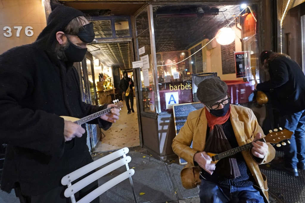 A band member, left, joins Olivier Conan, center, as the pair strum baglamas, stringed instruments from Greece and Turkey similar to lutes, outside th...