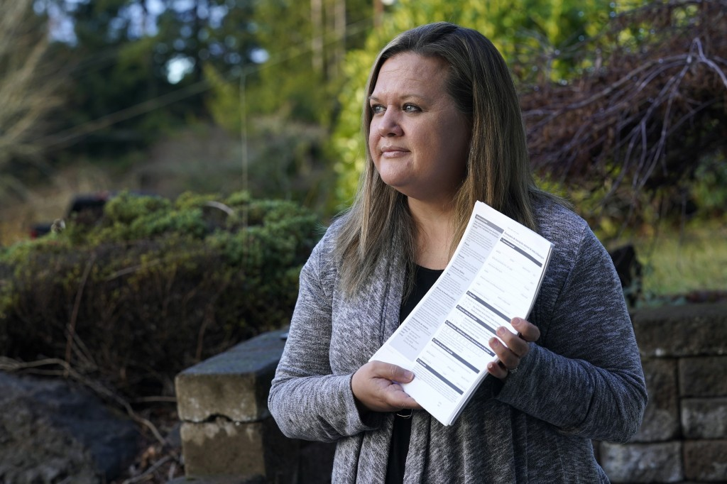Rep. Tarra Simmons, D-Bremerton, holds blank voter registration forms as she poses for a photo Wednesday, Dec. 9, 2020, at her home in Bremerton, Wash...