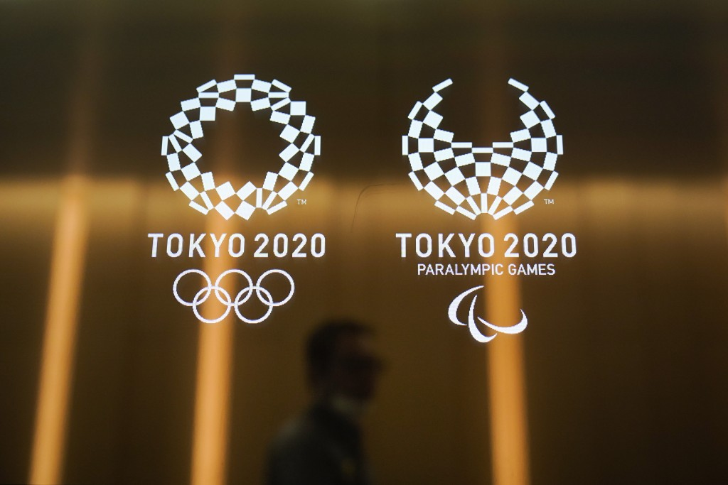 FILE - In this June 11, 2019, file photo, a man walks past the Tokyo 2020 Olympic logos in Tokyo. The U.S. Olympic and Paralympic Committee heeded cal...
