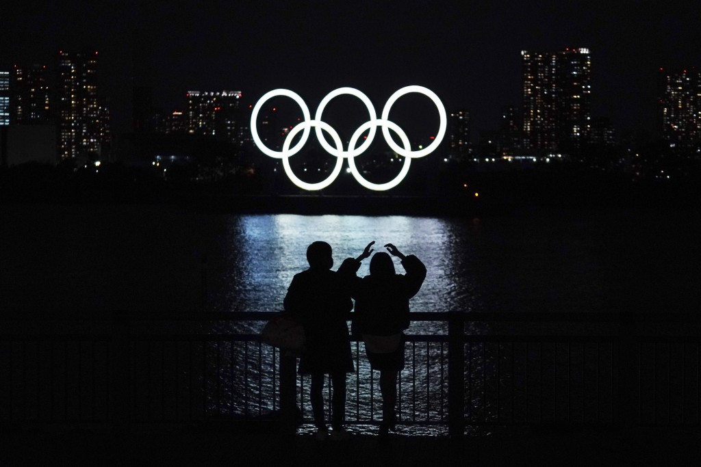 FILE - In this Dec. 1, 2020, file photo, a man and a woman look at the Olympic rings float in the water in the Odaiba section in Tokyo. The U.S. Olymp...