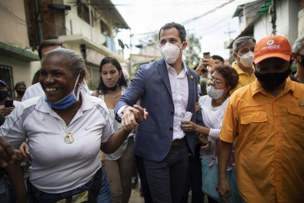 Venezuelan opposition leader Juan Guaidó holds hands with supporters during a visit to La Lucha neighborhood of Caracas, Venezuela, Thursday, Dec. 10,...