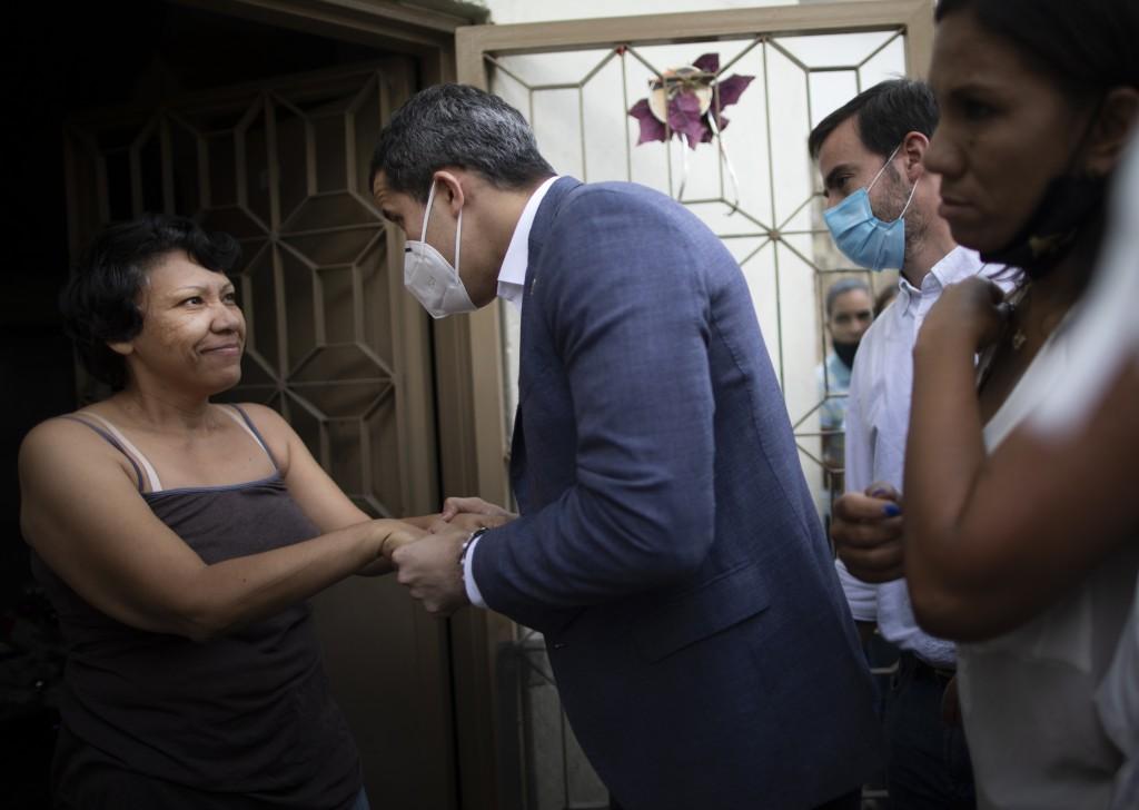 Venezuelan opposition leader Juan Guaidó talks with a resident during a visit to La Lucha neighborhood of Caracas, Venezuela, Thursday, Dec. 10, 2020....
