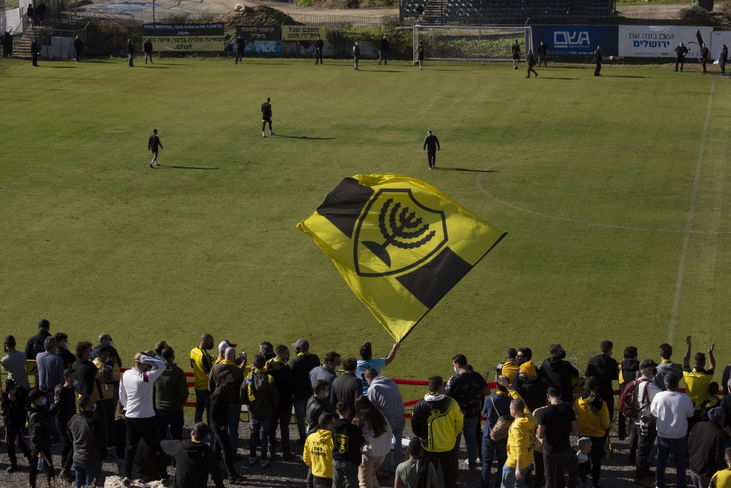 Beitar Jerusalem FC soccer supporters sing and wave their flag as players enter the pitch during a team training session in Jerusalem, Friday, Dec. 11...