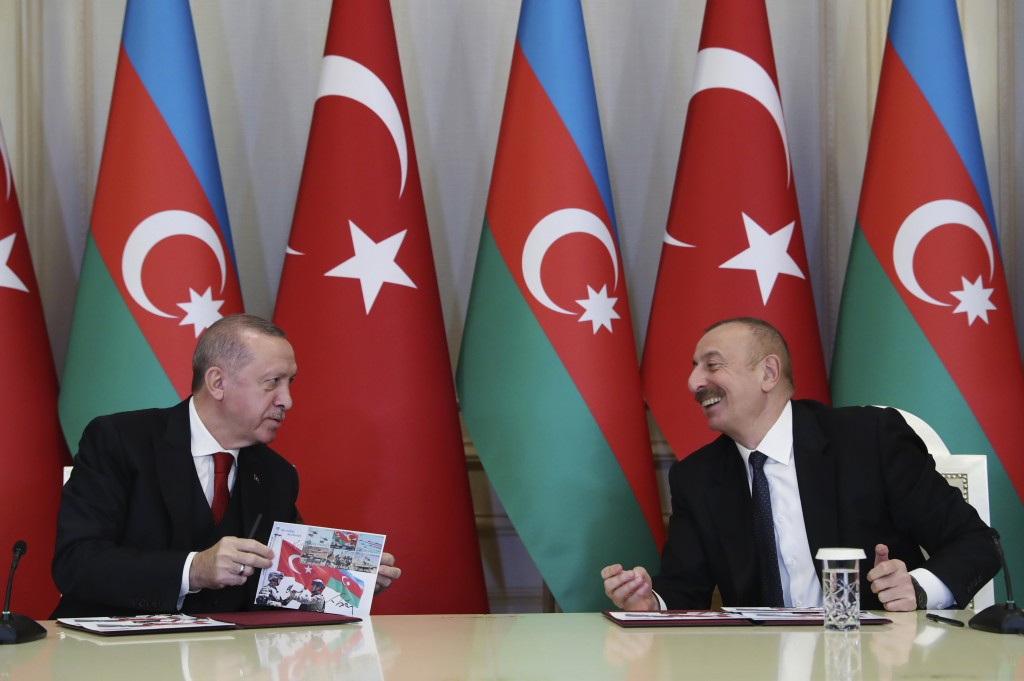 Turkey's President Recep Tayyip Erdogan, left and Azerbaijan's President Ilham Aliyev, right, talk during a joint news conference following their meet...