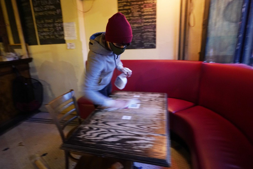 Bartender Alex Wright sanitizes a table before opening Barbès, a popular neighborhood music venue and bar converted to a bottle shop and mostly-outdoo...