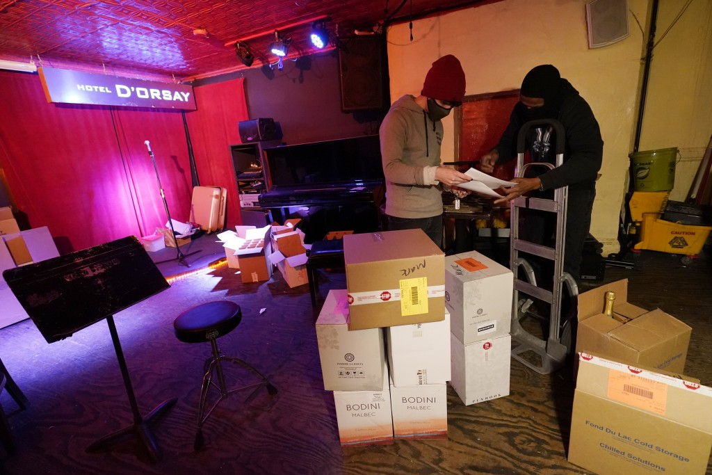 Bartender Alex Wright, left, reviews paperwork on a wine delivery at Barbès, a popular music venue and bar that has been converted to a bottle shop to...