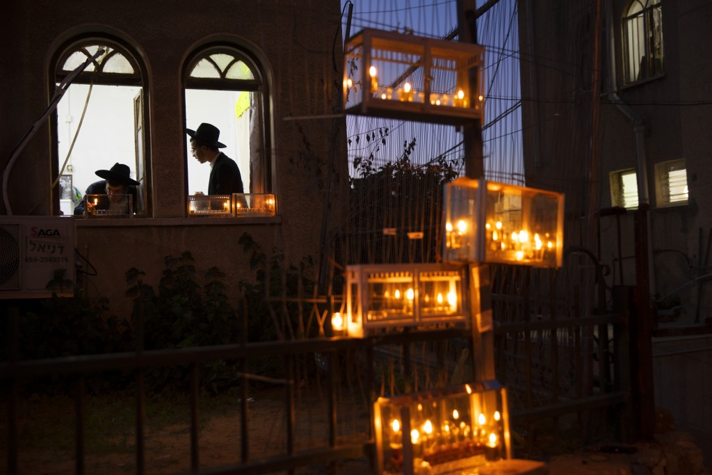 Ultra-Orthodox Jewish yeshiva students light candles on the first day of the Jewish holiday of Hanukkah in the ultra-Orthodox city of Bnei Brak near T...