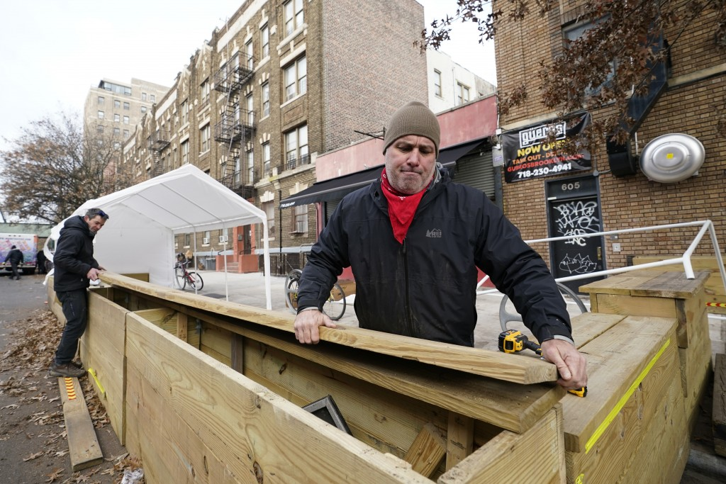 Wade Hagenbart, right, lifts the top off a wooden support barrier for a tent he's constructing for outdoor dining Guero's, the tiny but popular taco a...