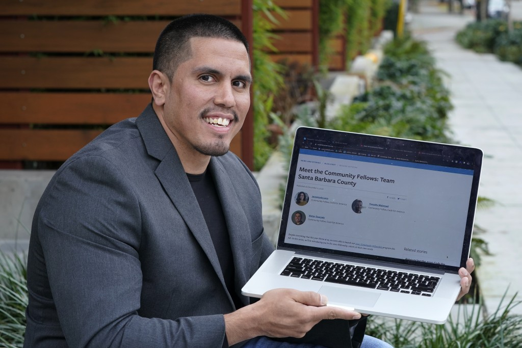 Victor Sauceda holds his laptop computer as he poses for a photo outside his apartment building Thursday, Dec. 3, 2020, in Seattle. While serving eigh...
