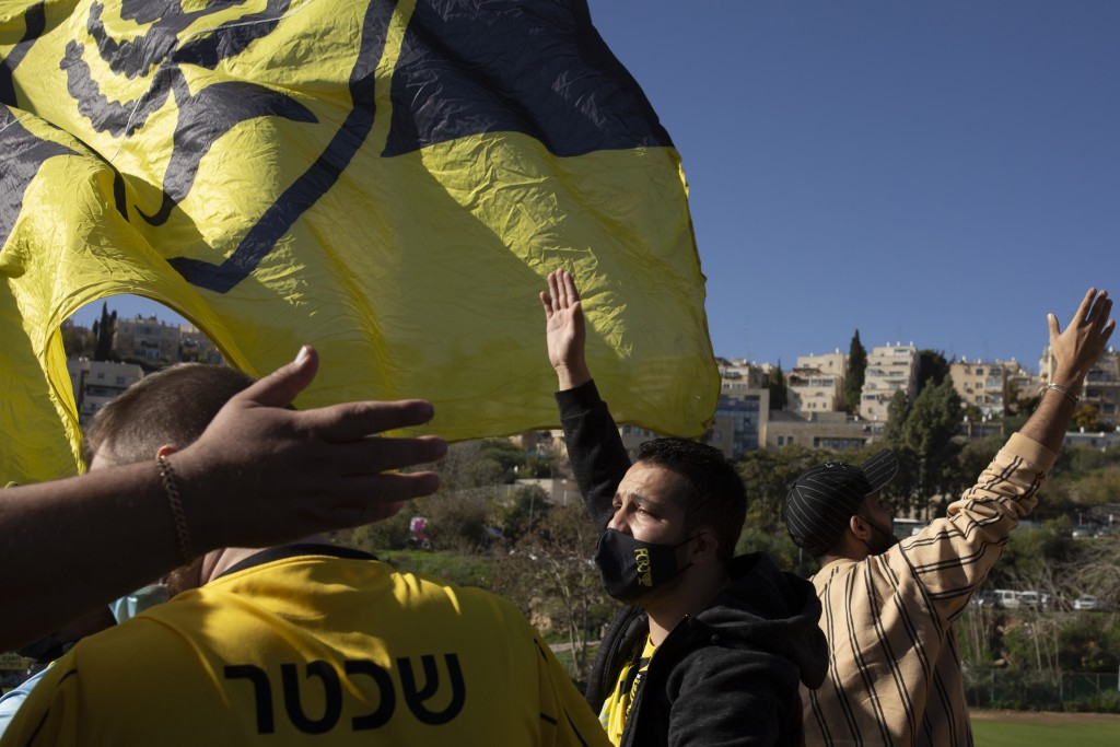 Beitar Jerusalem FC soccer supporters sing and wave their flag during a team training session in Jerusalem, Friday, Dec. 11, 2020 days after the club ...
