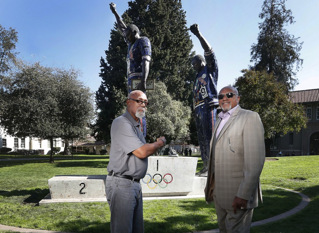 FILE - In this Oct. 17, 2018, file photo, John Carlos, left, and Tommie Smith pose for a photo in front of statue that honors their iconic, black-glov...