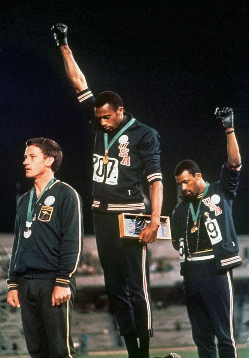 FILE - In this Oct. 16, 1968, file photo, U.S. athletes Tommie Smith, center, and John Carlos extend gloved hands skyward in racial protest during the...