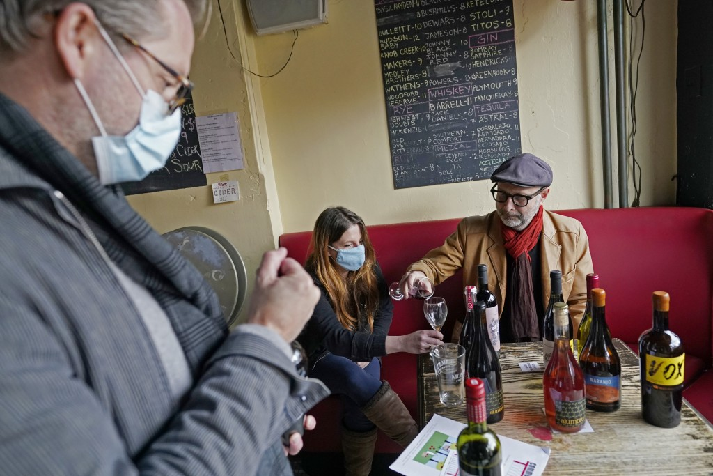 Wine salesman Jeff Hansen, left, replaces the cork on a bottle of wine after pouring samples for Barbès retail manager Hanna Cheek, center, and owner ...