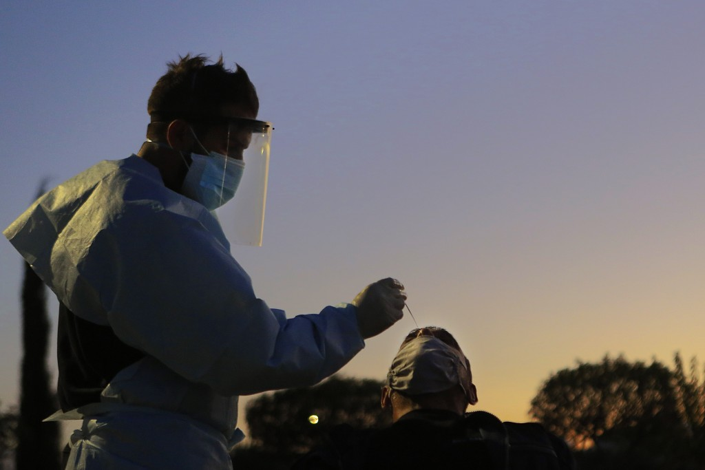 A health worker carries out a rapid coronavirus test at a car-parking in Lakatamia a suburb west of capital Nicosia, Cyprus, Thursday, Dec. 10, 2020. ...