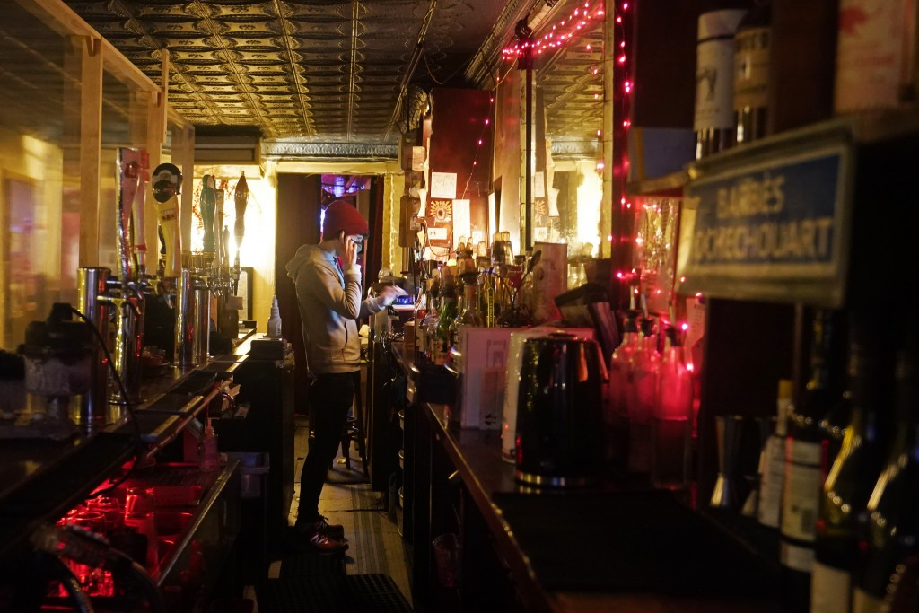 Bartender Alex Wright takes a phone order for liquor on his cell phone while tending the bar behind a protective plastic barrier separating him from p...