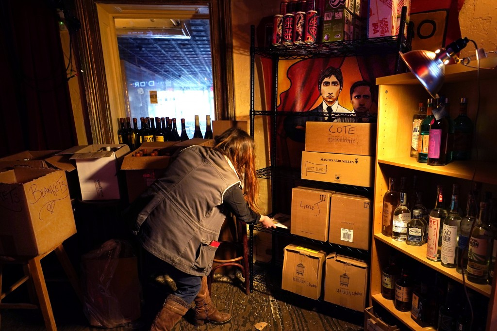 Hanna Cheek clears space on a shelf while organizing storage for wine and liquor in the now-idle performance space at Barbès, a popular neighborhood m...