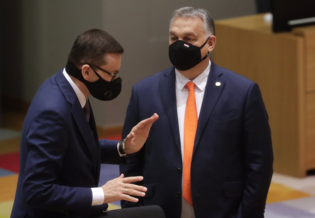 Poland's Prime Minister Mateusz Morawiecki, left, speaks with Hungary's Prime Minister Viktor Orban during a round table meeting at an EU summit at th...