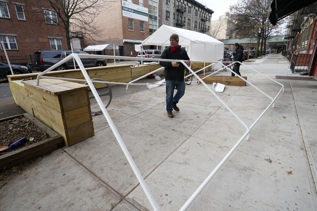 Wade Hagenbart lifts plastic piping for a tent while building a winter shelter for patrons of Guero's, the popular taco and margarita restaurant he co...