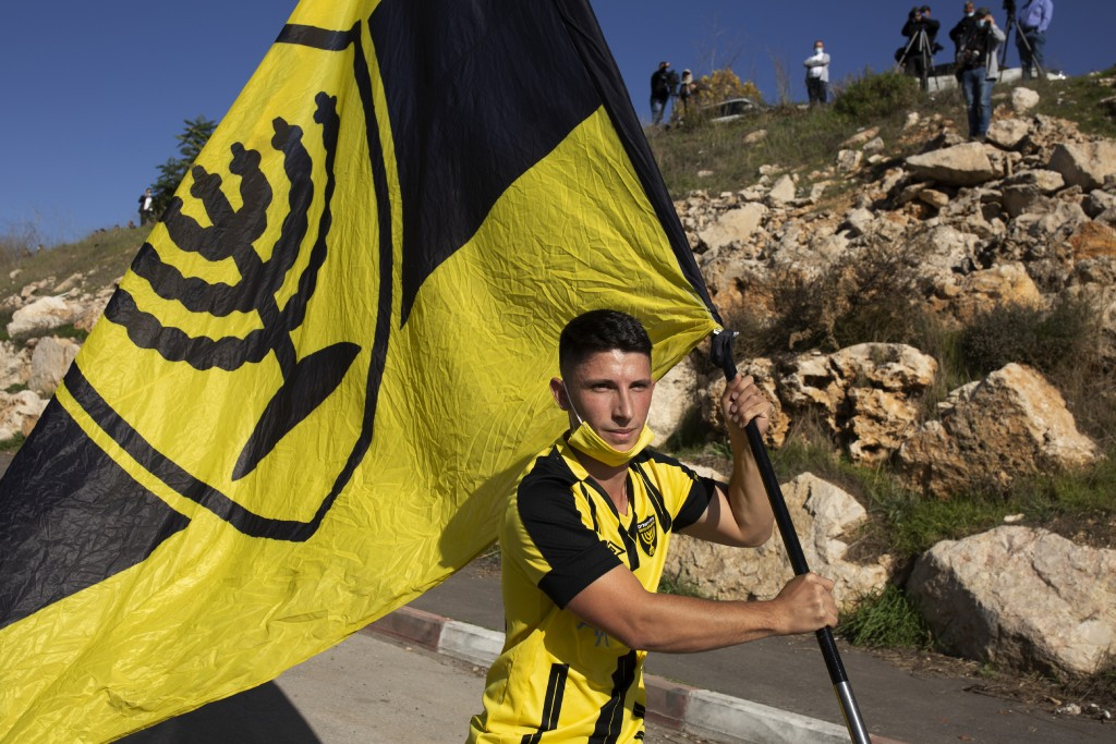 A Beitar Jerusalem FC soccer supporter carries their flag during a team training session in Jerusalem, Friday, Dec. 11, 2020, days after the club anno...