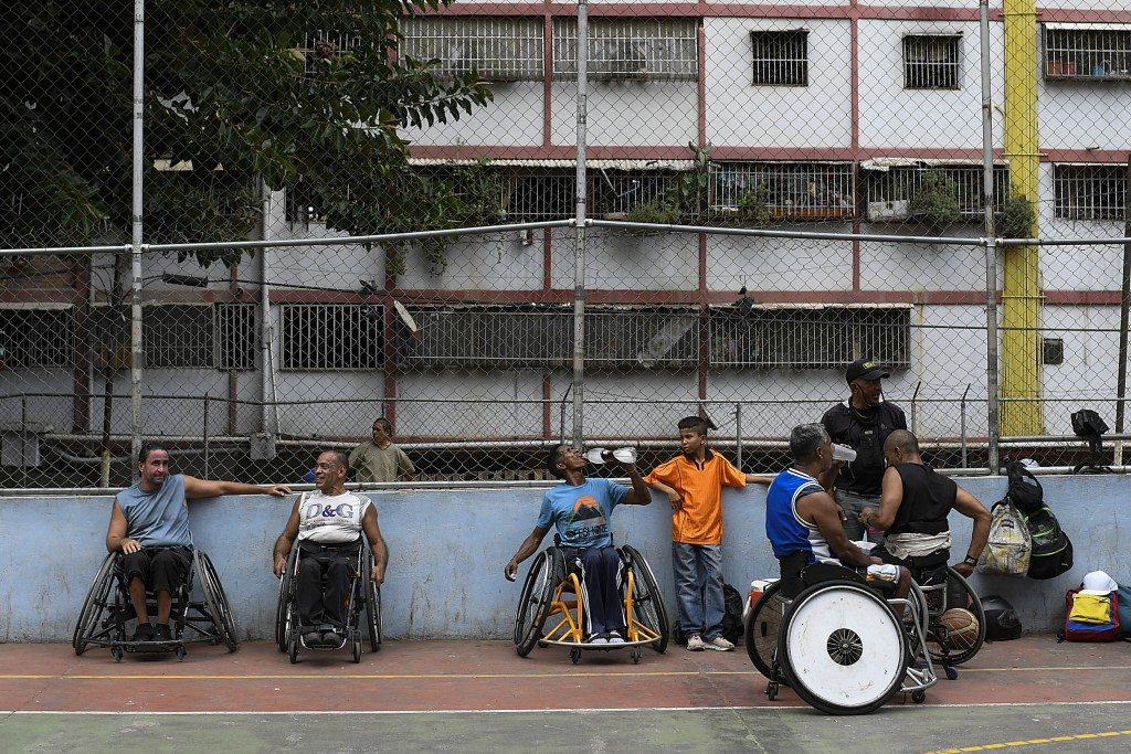 Manuel Mendoza takes a break with his wheelchair-bound friends after basketball game at a public court in the Artigas neighborhood of Caracas, Venezue...