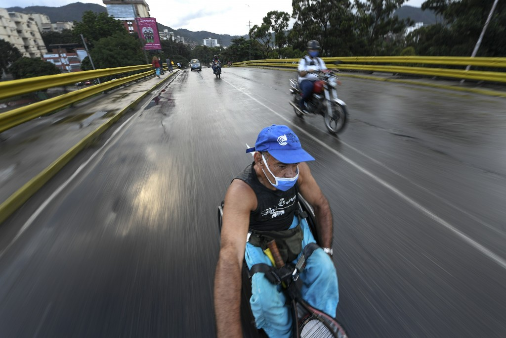 Manuel Mendoza hitches a ride in his wheelchair by grabbing on to the back of a motorcycle in the La Paz neighborhood of Caracas, Venezuela, Monday, N...