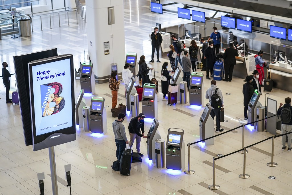 FILE - In this Nov. 25, 2020, file photo, travelers wait to check-in for their flights ahead of Thanksgiving at LaGuardia Airport, in the Queens borou...