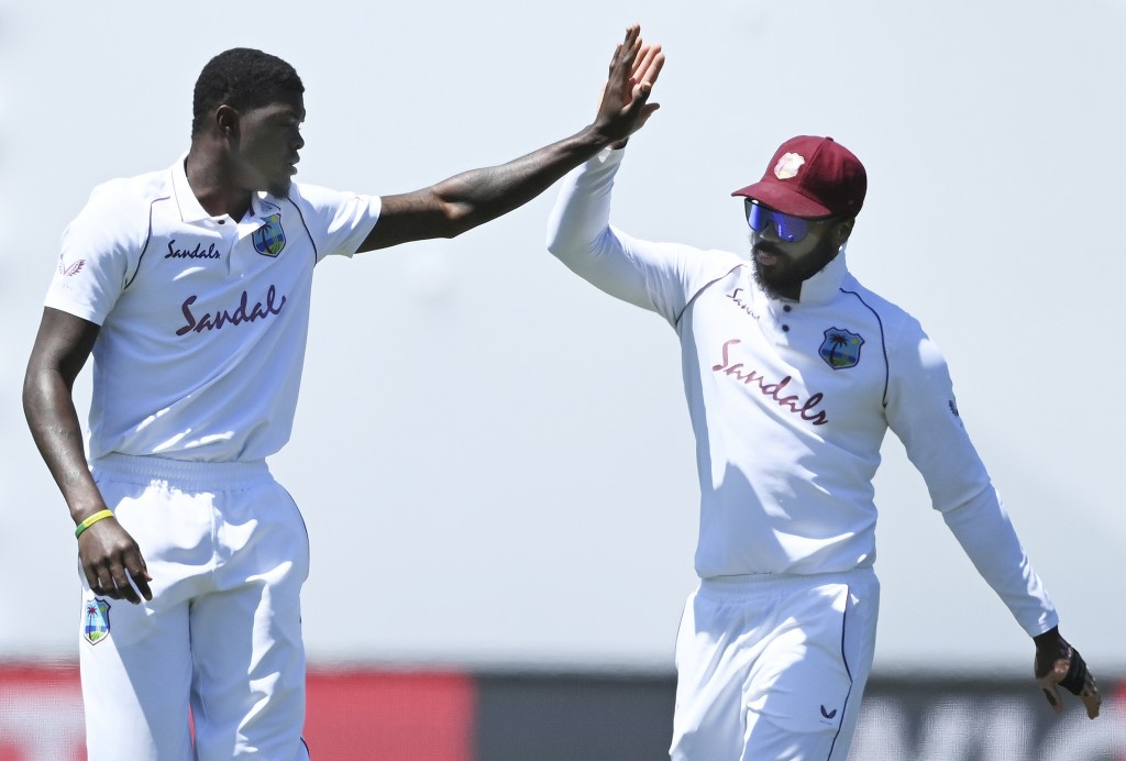 The West Indies' Alzarri Joseph, left, celebrates with teammate John Campbell after the wicket of New Zealand's Kyle Jamieson for 20 runs during play ...