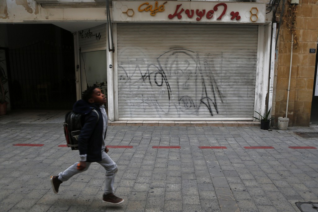 A boy runs past a closed cafe in the medieval core of central capital Nicosia, Cyprus, Friday, Dec. 11, 2020. Cyprus' Health Minister Constantinos Ioa...