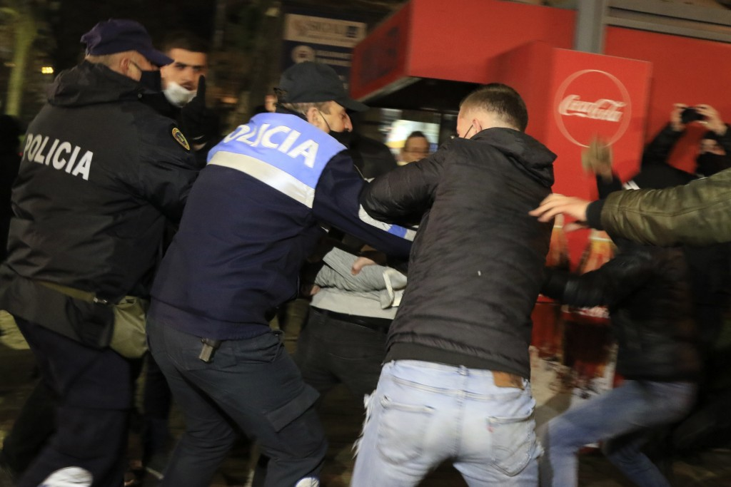 Albanian police detain a protester as others try to release him during clashes in Tirana, Friday, Dec. 11, 2020. Albanian demonstrators clashed in the...