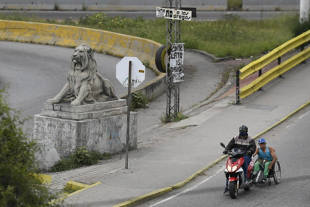 Manuel Mendoza hitches a ride in his wheelchair by grabbing on to the back of a motorcycle in the La Paz neighborhood of Caracas, Venezuela, Saturday,...