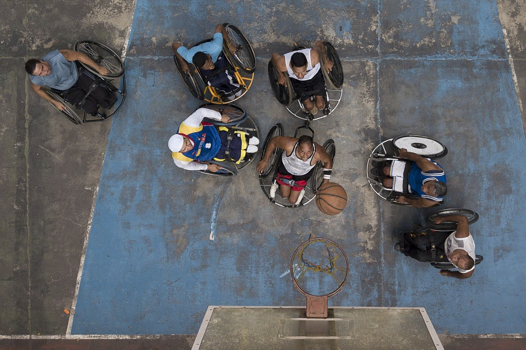 Manuel Mendoza plays basketball with his wheelchair-bound friends at a public court in the Artigas neighborhood of Caracas, Venezuela, Saturday, Oct. ...
