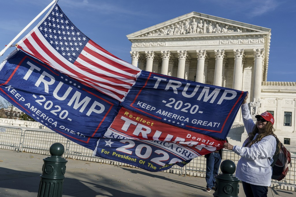 Kathy Kratt of Orlando, Fla., displays her Trump flags as she and other protesters demonstrate their support for President Donald Trump at the Supreme...
