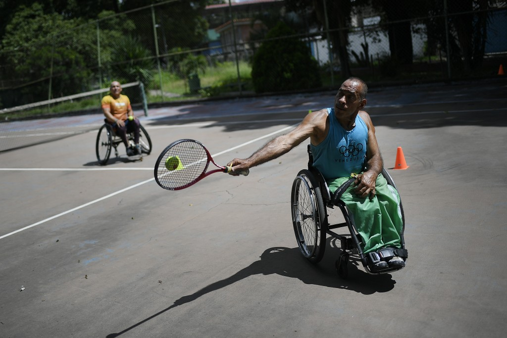 Manuel Mendoza plays tennis during a training session with a wheelchair-bound friend at the La Paz tennis center in La Paz neighborhood of Caracas, Ve...