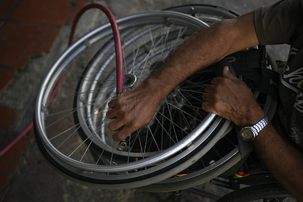 Manuel Mendoza inflates wheelchair tires at a car workshop, before a tennis practice at La Paz tennis center in the La Paz neighborhood of Caracas, Ve...
