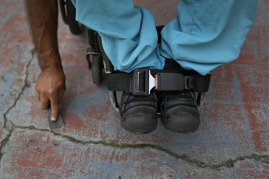 Manuel Mendoza cleans a tennis court after fastening his feet to his wheelchair with a car seat belt at the La Paz tennis center in La Paz neighborhoo...