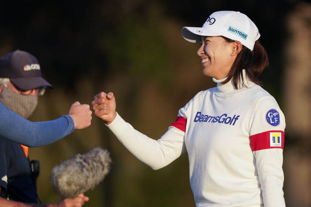 Hinako Shibuno, of Japan, fist bumbs fellow players after her round of golf during the third round of the U.S. Women's Open golf tournament, Saturday,...