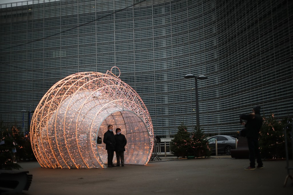 Passers by pose for a photograph next to Christmas decorations placed outside the European Commission headquarters in Brussels, Saturday, Dec. 12, 202...