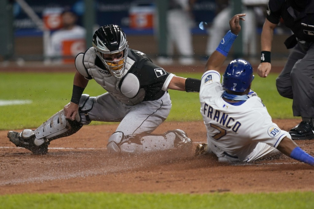 FILE - In this Sept. 4, 2020, file photo, Chicago White Sox catcher James McCann, left, misses the tag on Kansas City Royals' Maikel Franco (7), who s...