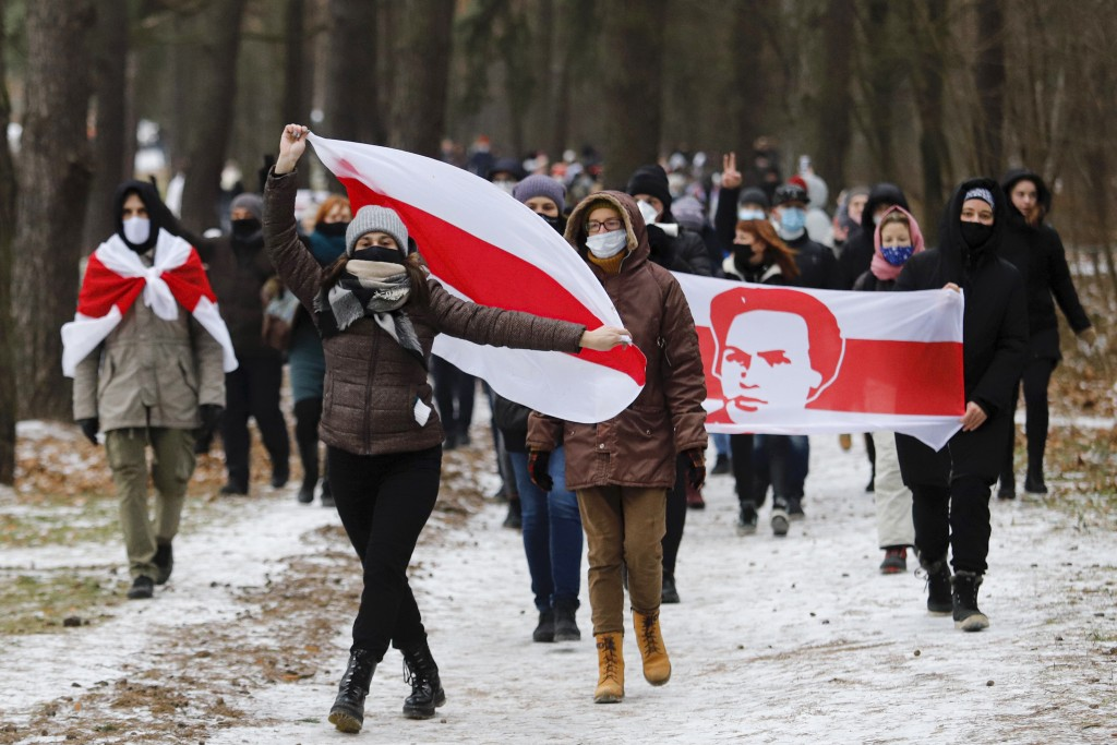 Demonstrators wearing face masks to help curb the spread of the coronavirus carry old Belarusian national flags during an opposition rally to protest ...