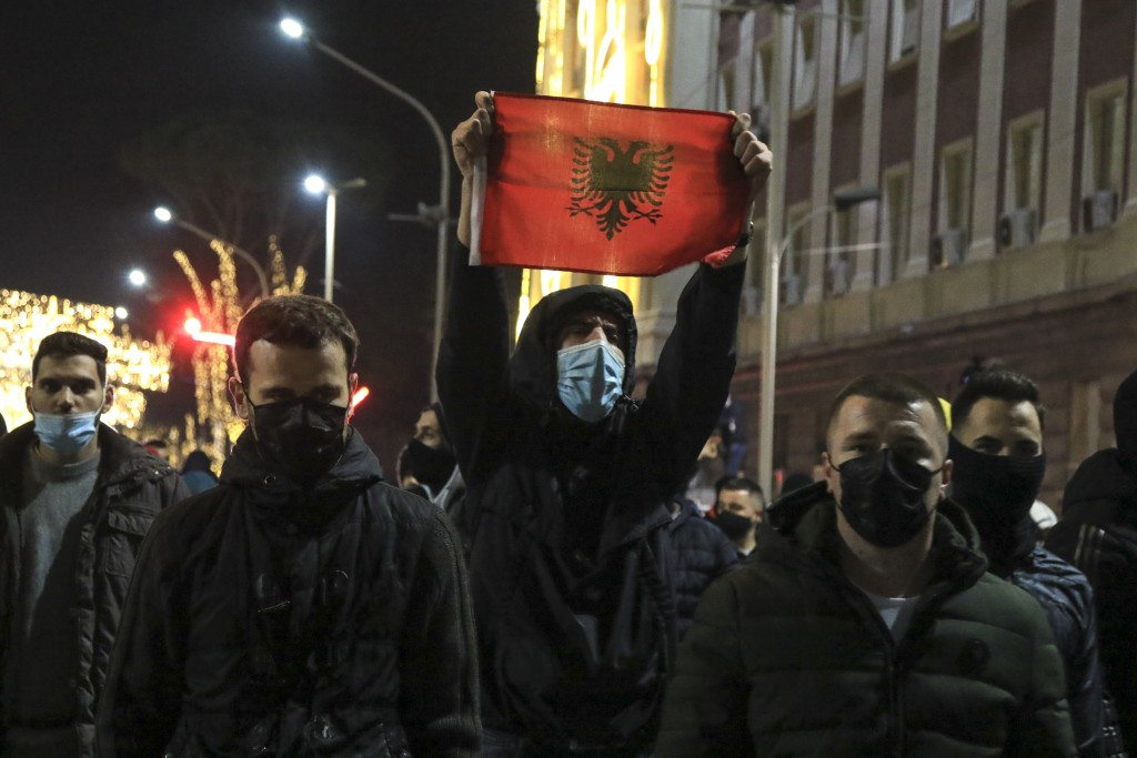Protesters take part in a protest rally in Tirana, Saturday, Dec. 12, 2020. Demonstrators in a northern Albanian city damaged the left-wing governing ...