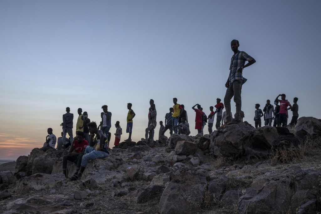 People who fled the conflict in Ethiopia's Tigray region, stand on a hill top over looking Umm Rakouba refugee camp in Qadarif, eastern Sudan, Thursda...