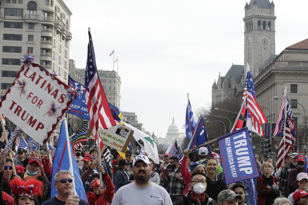 With the U.S. Capitol building in the background, supporters of President Donald Trump demonstrate during a rally at Freedom Plaza, Saturday, Dec. 12,...