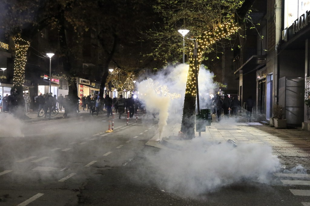 Albanian protesters run away from teargas during a protest rally in Tirana, Saturday, Dec. 12, 2020. Demonstrators in a northern Albanian city damaged...