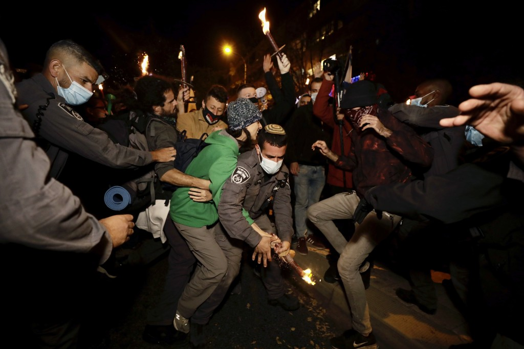 Israeli protesters scuffle with police officers during a demonstration against Israeli Prime Minister Benjamin Netanyahu in Jerusalem, Saturday, Dec. ...